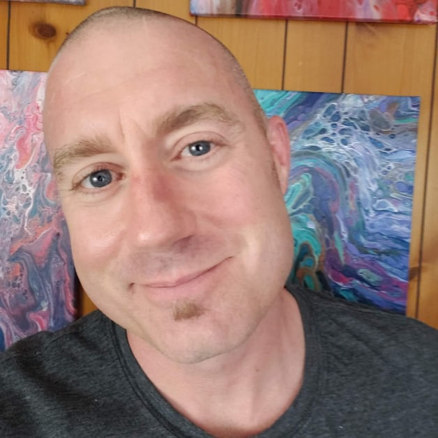 Headshot of Brian with colorful abstract paintings behind him